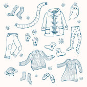 Winter clothing set of vector illustrations. Collection of warm clothes: jumper, coat, scarf, gloves and hats in hand drawn style