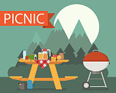 Summer wooden picnic table on mountain night background. Family barbecue concept with picnic party stuff. Bbq grill, cooking pan, drink and food for outing on forest.