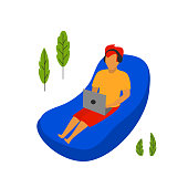young man working on a laptop lying on inflatable lounge hammock