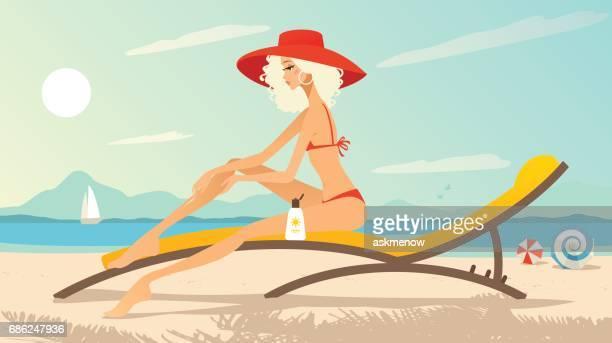 Junge Frau am Strand Sonnenmilch eincremen