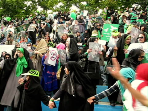 9 Jun 2009 WS HA PAN Female protestors holding placards and posters during demonstration on street / Teheran Iran / AUDIO
