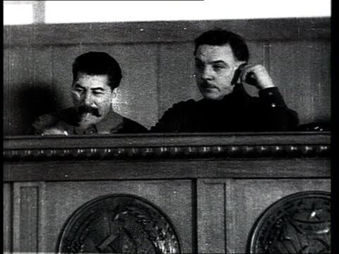 Joseph Stalin reciving rifle as gift at XVII Party Congres meeting delegates clapping / Moscow Russia
