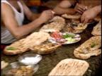 August 2004 Closeup Afghan soldiers eating meal around table/ Afghanistan