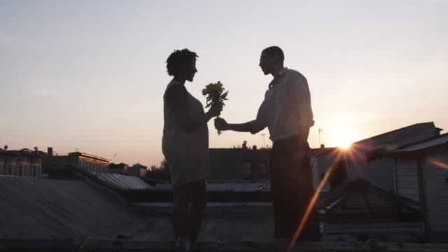 WS, Lockdown, A man giving flowers to a woman on a rooftop terrace at sunset