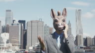 'MS, Lockdown, Businessman wearing a donkey mask and using a mobile phone, New York City, USA'