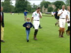 Prince Harry walks with Prince Charles in polo gear across fields with other polo players Cirencester 13 Jul 91