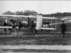 VIEW soldiers pushing Wright brothers' airplane on field / documentary