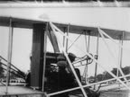 Orville Wright starting propeller as Lt Frank Lahm sits in airplane / documentary