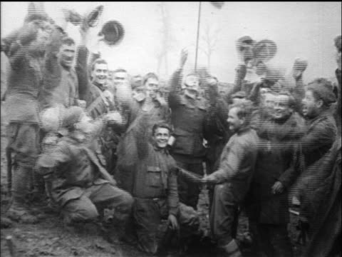 B/W 1918 happy soldiers throwing hats in air on Armistice Day / tilt up to US flag / WW I