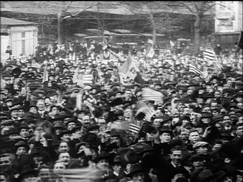 B/W 1918 high angle PAN crowd cheering waving US flags during Armistice Day celebration / WW I
