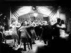 B/W 1920s wide shot people dancing in speakeasy / Prohibition / newsreel