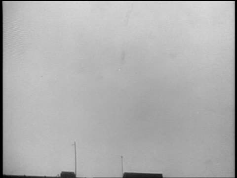 B/W 1939 long shot tilt down destroyed German airplane falling over Warsaw Poland / documentary