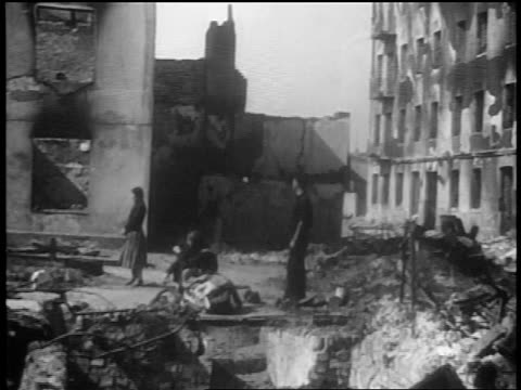 B/W 1939 tilt up people standing amidst rubble after German bombings / Warsaw Poland / documentary