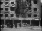 B/W 1939 tilt up people walking in front of bombed building after German invasion / Warsaw / documentary