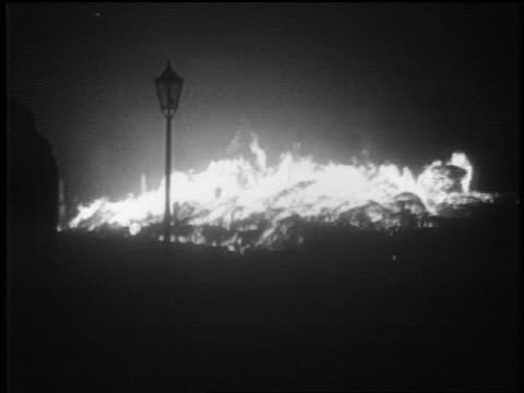 PAN lamppost in front of fires at night after German bombing / Warsaw Poland / docu
