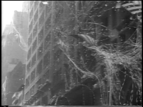 B/W 1938 tilt down confetti falling US flags in ticker tape parade for 'Wrong Way' Corrigan / NYC