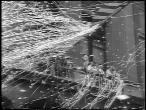 B/W 1938 low angle men waving from windows with ticker tape in parade for 'Wrong Way' Corrigan / NYC