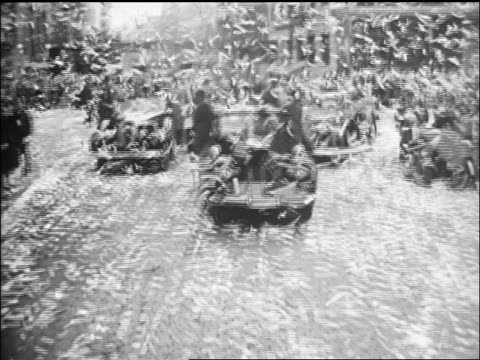 B/W 1945 rear car point of view ticker tape falling over cars in Navy Day Parade on NYC street / newsreel