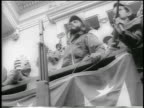 B/W 1959 low angle Fidel Castro enthusiastically giving speech from balcony / postrevolution Havana