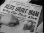 B/W 1961 close up hand on newspaper with 'Reds Orbit Man' headline photo of Yuri Gagarin