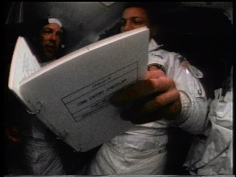 1970 three astronauts looking at manual in space capsule / Apollo 13