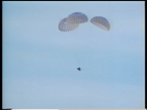 Apollo 13 space capsule attached to parachutes descending in blue sky
