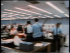 PAN crowd of office workers at desks standing watching television