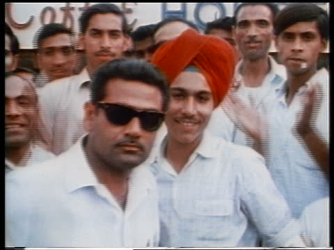 1970 crowd of Indian men smiling clapping outdoors / one man in turban