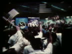 wide shot of crowd waving American flags at Mission Control