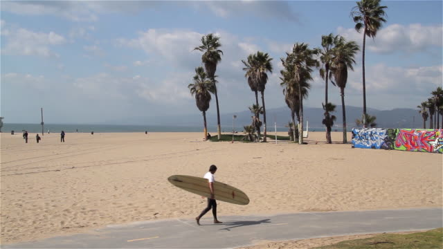 SURFER CARRYING SURFBOARD ON CYCLE PATH VENICE BOARDWALK