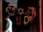 1938 medium shot pan storefronts of businesses w/AntiSemitic graffiti Star of David / Vienna Austria