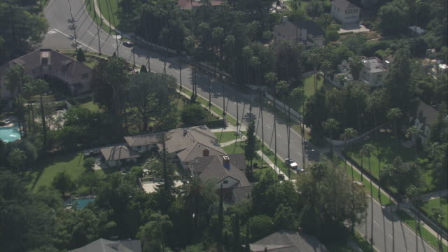 AERIAL OF CADILLAC ESCALADE HYBRID SUV DRIVING THROUGH UPPER CLASS RESIDENTIAL AREA. COULD BE SAN GABRIEL VALLEY OR PASADENA. SUBURBS. MANSIONS WITH LAWNS AND SWIMMING POOLS. PALM TREES. SUV STOPS AT STOP SIGN.