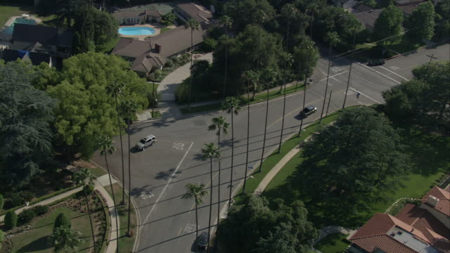 AERIAL OF CADILLAC ESCALADE HYBRID SUV DRIVING THROUGH UPPER CLASS RESIDENTIAL AREA. COULD BE SAN GABRIEL VALLEY OR PASADENA. SUBURBS. MANSIONS WITH LAWNS AND SWIMMING POOLS. PALM TREES. SUV MAKES SEVERAL U-TURNS IN NEIGHBORHOOD.