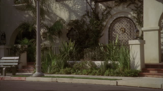 PAN UP FROM STREET TO MULTI-STORY SPANISH STYLE APARTMENT BUILDING. BALCONIES OR FIRE ESCAPES VISIBLE. LAMP POST AND BENCH VISIBLE IN FRONT OF APARTMENT BUILDING. TILE AND FOUNTAIN IN GARDEN AREA VISIBLE BEHIND FENCE OF BUILDING.TTPS://WWW.SO.