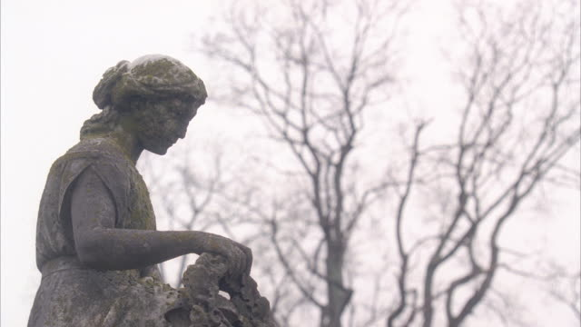 MEDIUM ANGLE OF STONE STATUE OF WOMAN. COULD BE ON GRAVESTONE OR MEMORIAL. BARE BRANCHES OF TREES IN THE BG.