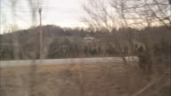 WIDE ANGLE MOVING POV THROUGH COUNTRYSIDE OR RURAL AREA. BARE BRANCHES ON TREES IN FOREST OR WOODS. SMALL TOWN. COULD BE POV FROM BOXCAR ON TRAIN.