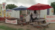 WIDE ANGLE OF FOOD STAND WITH PICNIC TABLES AND UMBRELLAS. SIGNS FOR SNOW CONES, BREAKFAST TACOS, AND DELI SANDWICHES. PEOPLE EATING AT PICNIC TABLE.