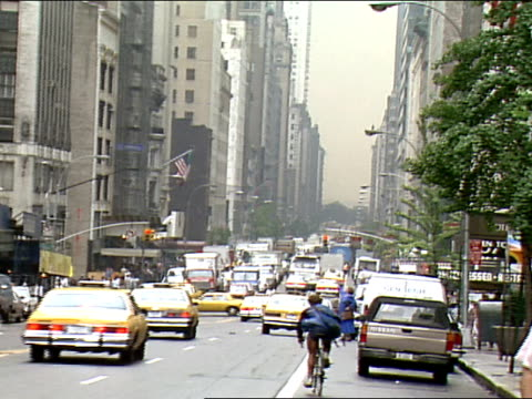 overcast summer day WS ZO LS Busy intersection twoway multilane street in Manhattan cars cabs and buses driving office buildings along street and...