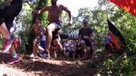 OBSTACLE RACERS START EVENT UP HILL TO COURSE CAMERA ON GROUND