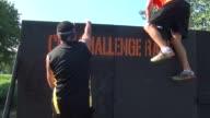RUNNING FAST AN OBSTACLE RACER QUICKLY GETS OVER AN EIGHT FOOT WALL AND CONTINUES ON