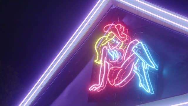 CLOSE ANGLE OF NEON COWGIRL SIGN.