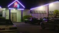 MEDIUM ANGLE OF STRIP CLUB. CARS IN PARKING LOT. NEON COWGIRL SIGN.