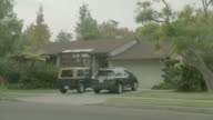 MEDIUM ANGLE OF CAR DRIVING ONTO DRIVEWAY OF MIDDLE CLASS SUBURBAN HOUSE.