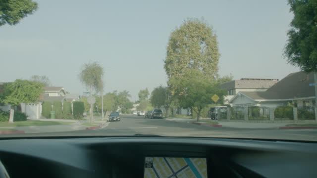MEDIUM ANGLE STRAIGHT FORWARD DRIVING POV FROM CAR WITH GPS SYSTEM OF SUBURBAN NEIGHBORHOOD.