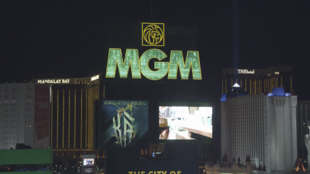 MEDIUM ANGLE OF MGM GRAND NEON SIGN WITH TELEVISION MONITOR. LUXOR, MADNALAY BAY, AND EXCALIBUR HOTEL AND CASINOS VISIBLE.