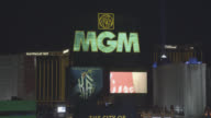 PAN LEFT TO RIGHT MEDIUM ANGLE TO MGM GRAND NEON SIGN IN FG.  LUXOR, MADNALAY BAY, AND EXCALIBUR HOTEL AND CASINOS VISIBLE IN BG.
