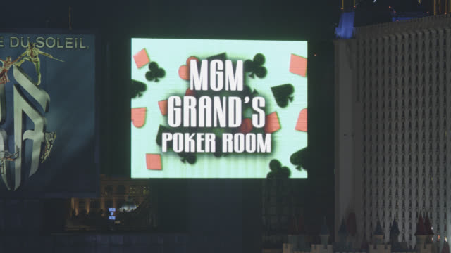 PAN LEFT TO RIGHT CLOSE ANGLE TO MGM GRAND NEON SIGN IN FG.  EXCALIBUR HOTEL AND CASINO VISIBLE IN BG.