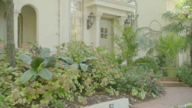 ZOOM IN ON UPPER CLASS HOUSE. PLANTS IN GARDEN.