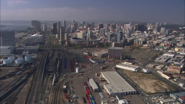 AERIAL OF SAN DIEGO CITY SKYLINE. HIGH RISE OFFICE AND APARTMENT BUILDINGS. RAILROAD OR TRAIN TRACKS.