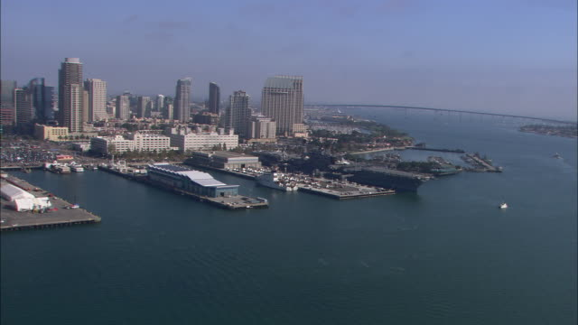 AERIAL OF USS MIDWAY, AIRCRAFT CARRIER AND NAVY SHIP. BOATS IN MARINA. DOCKS. CITY SKYLINE IN BG.